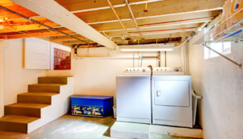 Old basement laundry room with old appliances.
